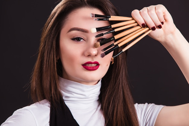 Makeup artist with brushes in hand on a black wall