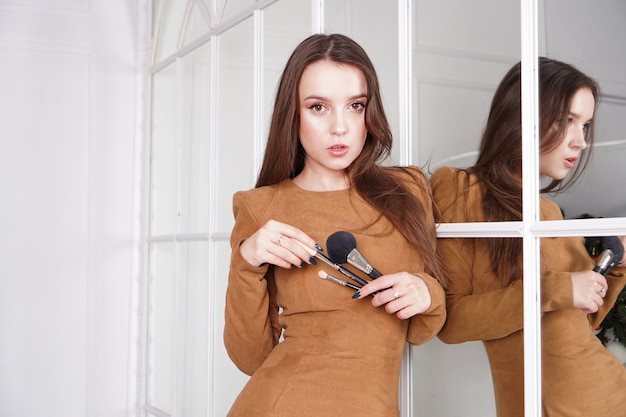 Makeup artist with long dark hair holding a powder brush, haughty expression