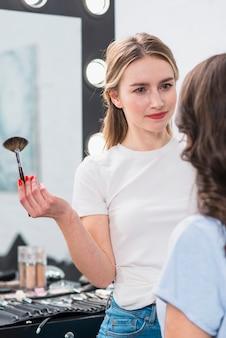 Makeup artist working with model in studio