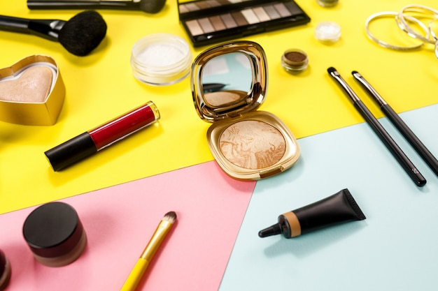 Makeup of beauty product on color surface.