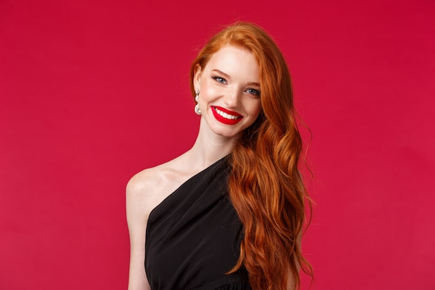 Makeup, beauty and women concept. close-up of elegant pretty redhead woman in luxurious slim black dress, red lipstick, smiling cheerful and pleased, attend formal event, party or romantic date