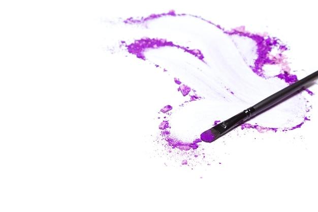メイクブラシと崩れた混合紫のアイシャドウテキスト用のさまざまな色合いのスペースメイクの背景