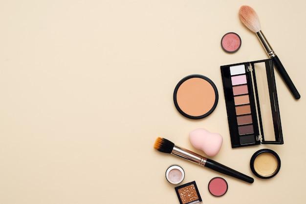 コピースペースのあるベージュの背景に化粧ブラシと装飾化粧品。