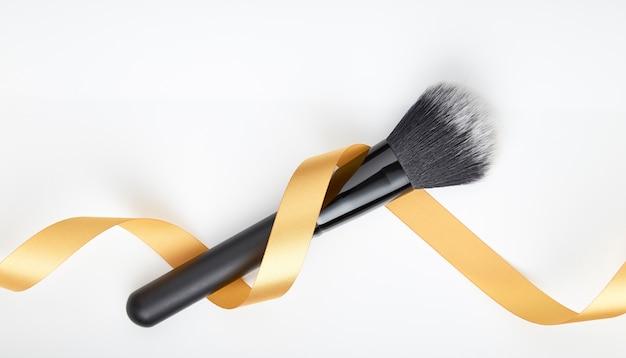 Кисть для макияжа и золотая лента