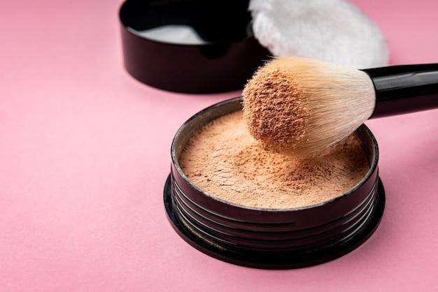Кисть для макияжа и пудра на розовом столе.