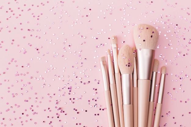 パステルピンクの背景に化粧ブラシと光沢のあるきらめく紙吹雪。お祭りメイクアクセサリーホリデーコンセプト。フラットレイ、上面図、コピースペース。