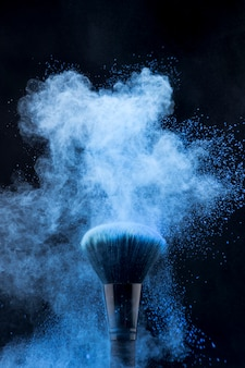 Makeup brush in blue powder burst on dark background