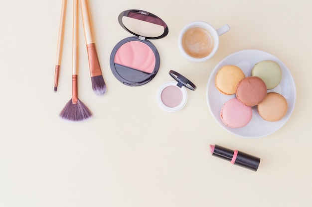 Makeup brush; blusher and lipstick with breakfast on colored background