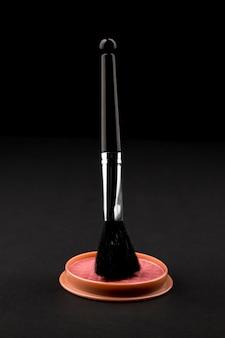 Makeup brush above compact blusher