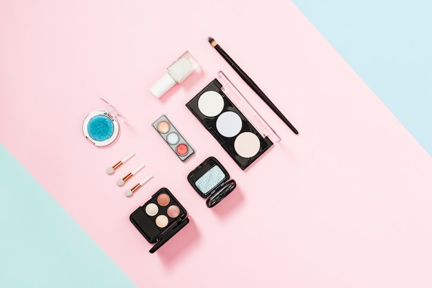 Spazzola di trucco e ombretto cosmetico tavolozza e compatto in polvere su sfondo rosa