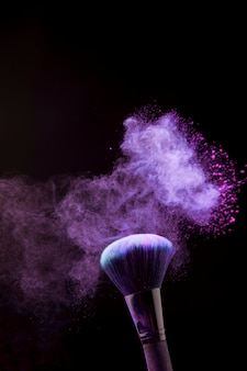 Makeup brush in mist of powder on dark background