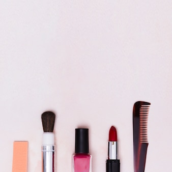 Makeup brush; nail varnish bottle; lipstick and comb on white textured backdrop