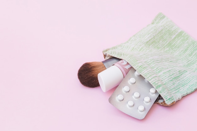 Makeup brush; nail varnish bottle and white pill blister pack inside the cotton pouch over pink background