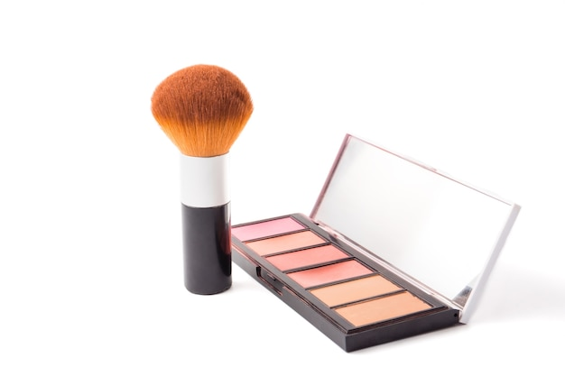Makeup brush and palette on white background.