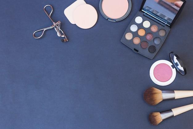 Косметическая кисточка; губка; румяна; палитра теней для век и бигуди для ресниц на синем фоне