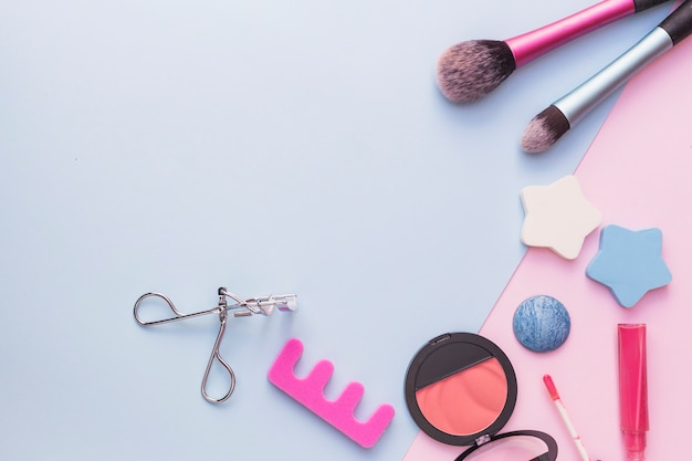 Makeup brush; star sponge; pink blusher; eyelash curler and lipstick on dual backdrop
