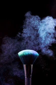 Makeup brush with blue powder mist