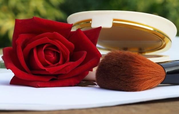 화장품 상자와 붉은 장미가 있는 메이크업 브러쉬