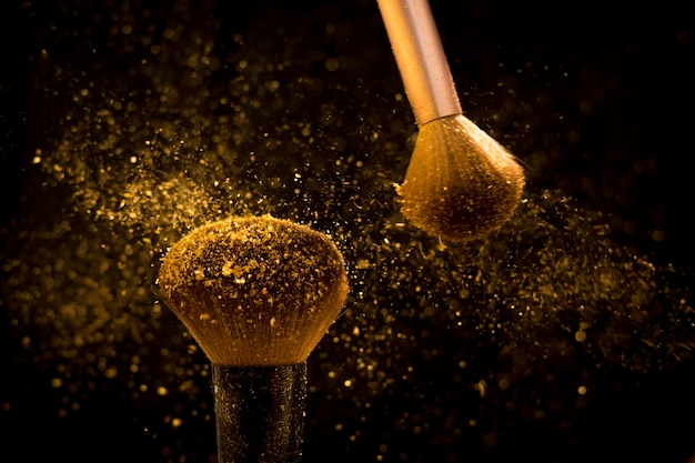Makeup brush with golden cosmetic powder spreading on black background