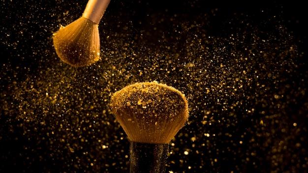 Кисть для макияжа с золотой косметической пудрой на черном фоне
