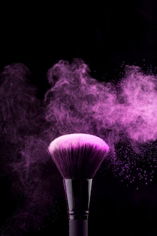 Makeup brush with neon fuchsia powder mist