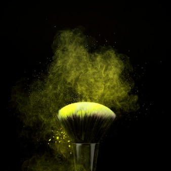 Makeup brush with neon green powder mist