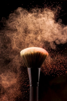 Makeup brush with peach color powder splash
