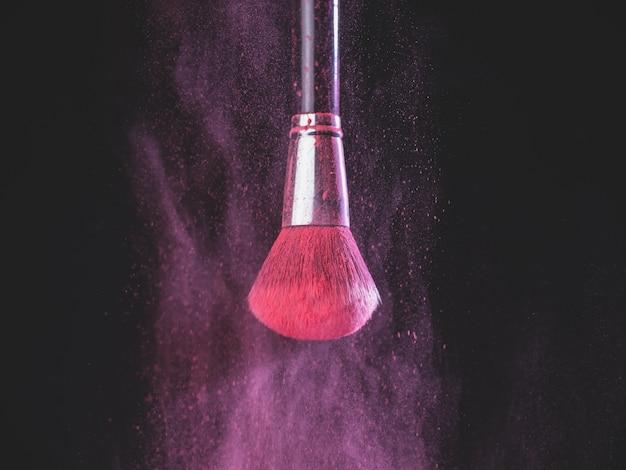 黒の背景にピンクの粉の爆発と化粧ブラシ