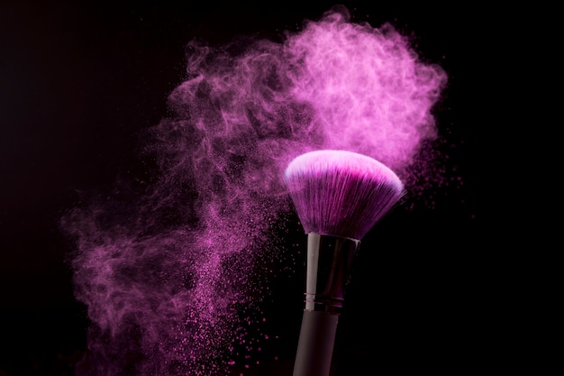 Makeup brush with purple powder dust on dark background
