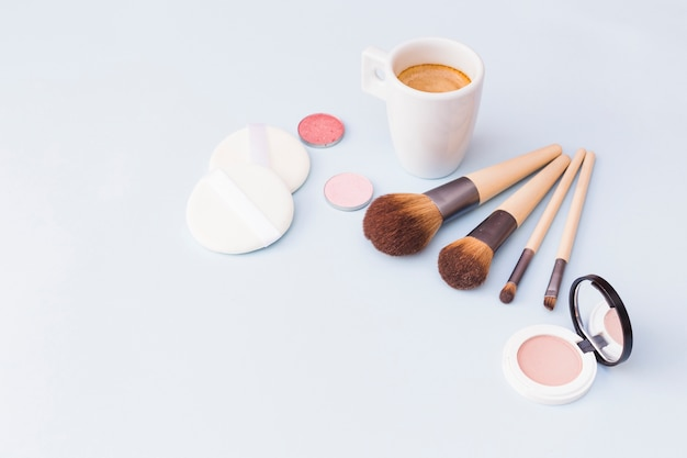 Makeup brush with sponge; eyeshadow and blusher with coffee mug on white background