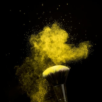 Makeup brush in yellow powder dust on dark background