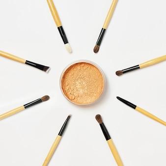 Кисти для макияжа выстроены по кругу вокруг открытой баночки с пудрой на белом. различные профессиональные кисти для макияжа, изолированные на белом в студии. инструменты визажиста. flatlay, вид сверху.