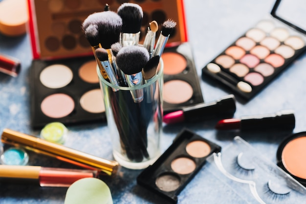Makeup brushes are on the table with decorative cosmetics in the background