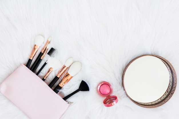 Makeup brushes in bag with pink compact powder and round mirror on fur backdrop