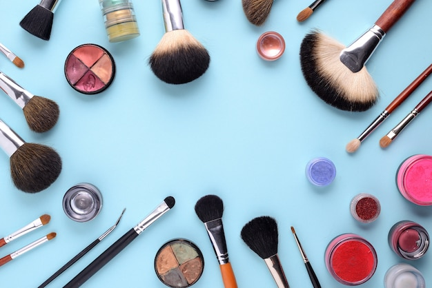 Makeup brushes on blue background with top view in flat lay