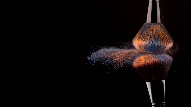 Makeup brushes and bright powder on dark background