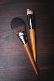 Makeup brushes on brown wooden surface