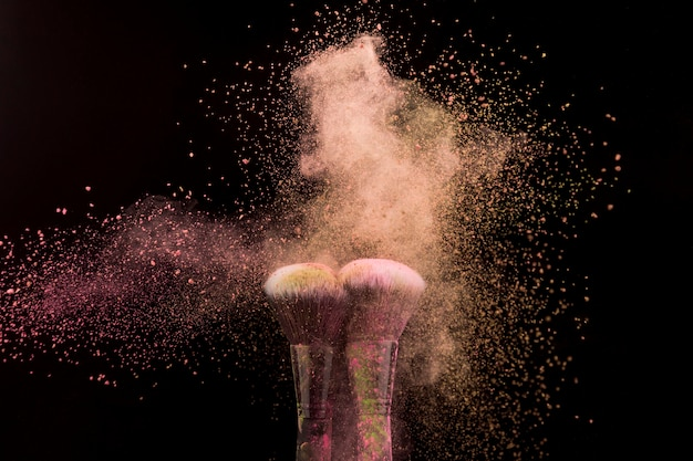 Makeup brushes in burst of beige powder on dark background