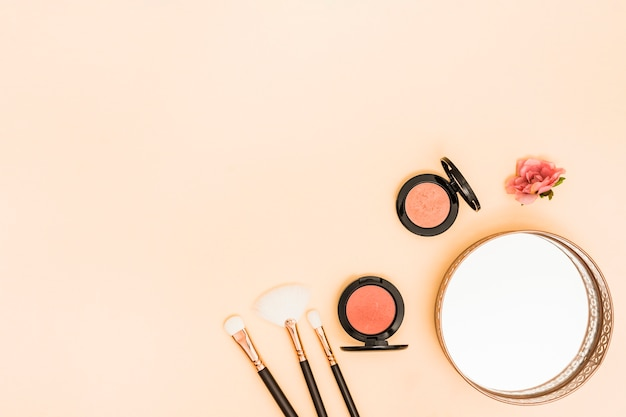 Makeup brushes; compact face powder; rose and mirror on the corner of colored backdrop