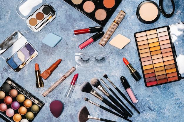 Кисти для макияжа, декоративная косметика, накладные ресницы на синем фоне. вид сверху