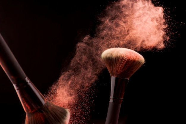 Makeup brushes in dust of red powder on dark background