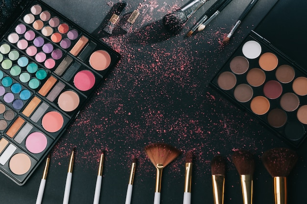 Makeup brushes and eye shadow on black background