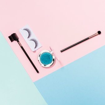 Makeup brushes; eyelashes and blue eyeshadow on pink; blue and light green backdrop