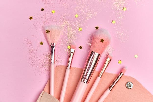 Кисти для макияжа в косметичке и блестящие блестки на розовой поверхности