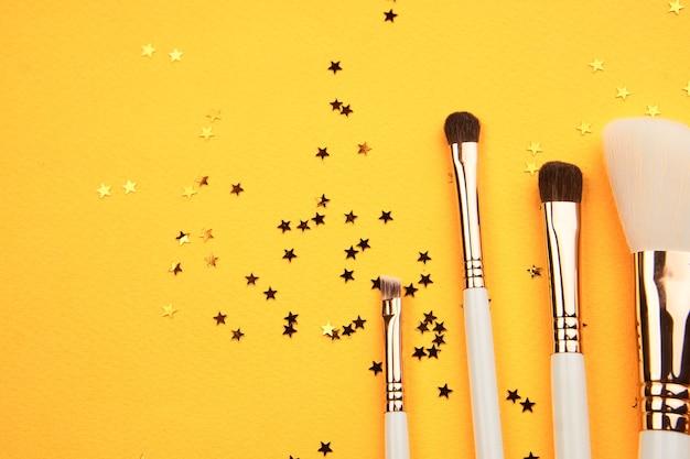 노란색 배경과 반짝이 자른 모양에 다양한 크기의 메이크업 브러쉬.