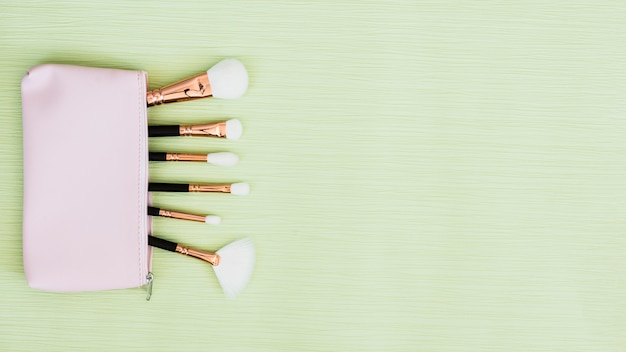 Makeup brushes inside the open bag on mint green background