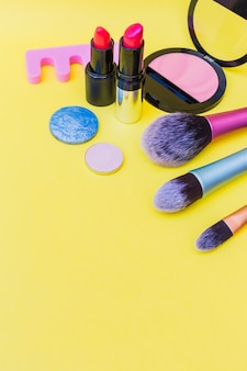 Makeup brushes; lipstick; and eye shadow; pink blusher and toe divider on yellow background