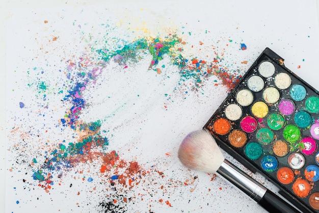 カラフルな顔料パウダーと白い背景の上の化粧ブラシ Premium写真