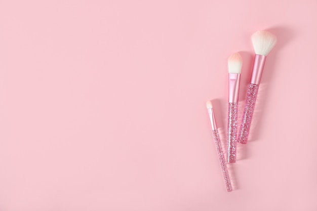 Makeup brushes on a pink background. place for text