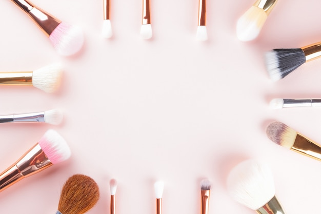 Makeup brushes on pink background. set of golden makeup brushes, concept. woman beauty accessory in pastel colors. copy space. flat lay